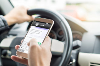 Texting while driving car. Irresponsible man sending sms and using smartphone. Writing and typing message with cellphone in vehicle.